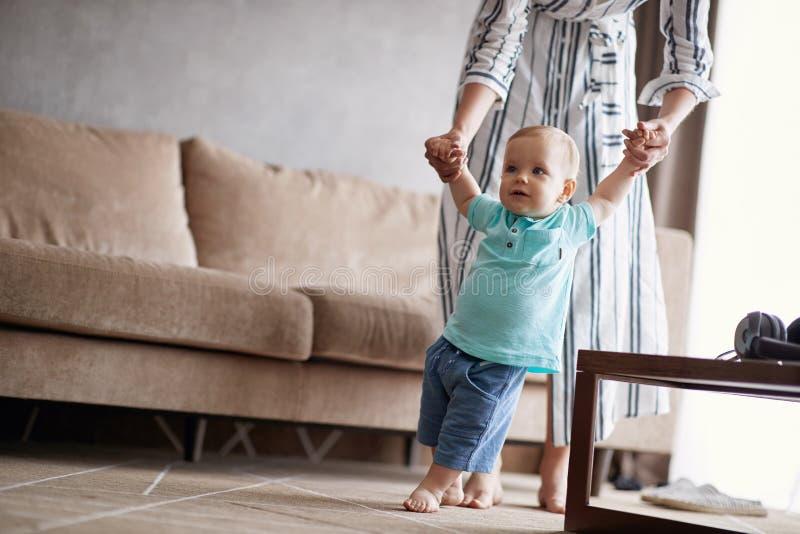 Het glimlachen baby leren die met moeder, kind lopen geniet van de sparren royalty-vrije stock afbeeldingen