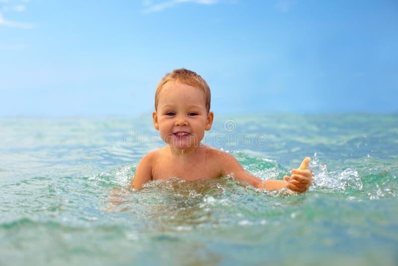 Het glimlachen babyjongen het spelen met overzees water stock afbeelding