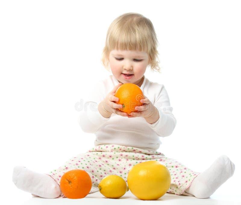 Het glimlachen babymeisje het spelen met vruchten stock fotografie