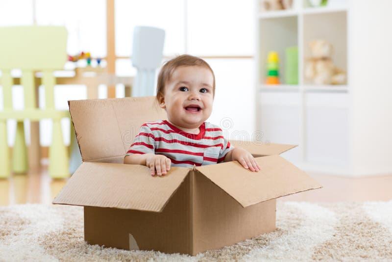 Het glimlachen babyzitting binnen kartondoos na zich het bewegen aan een nieuwe flat stock afbeelding