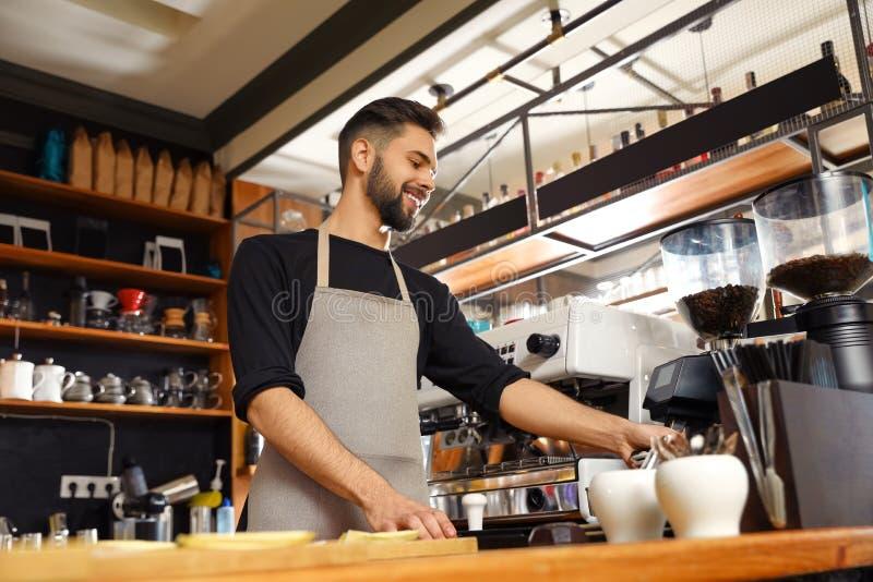 Het glimlachen barista dichtbij koffiemachine in koffie stock foto