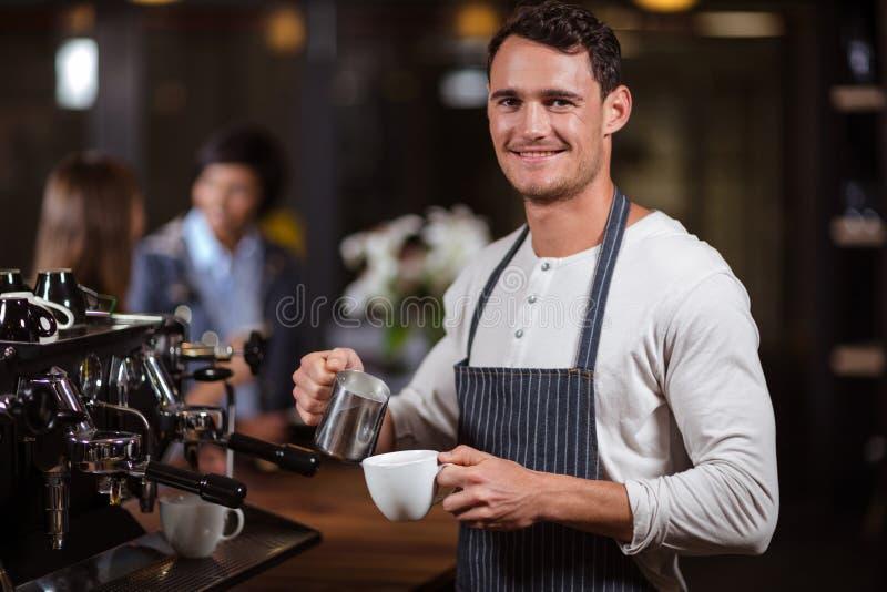 Het glimlachen barista die cappuccino voorbereiden stock foto's