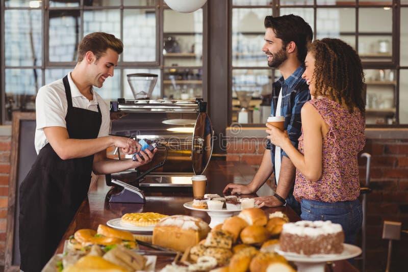 Het glimlachen barista die creditcard van hipsters nemen stock afbeelding
