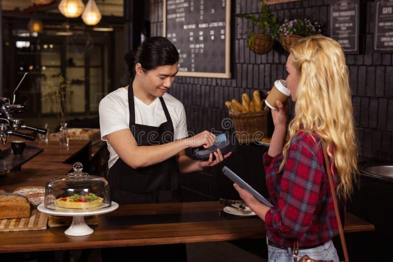 Het glimlachen barista die creditcard van klant nemen stock foto