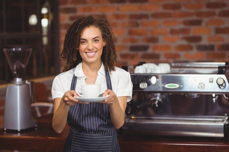 Het glimlachen barista die kop van koffie tonen stock fotografie
