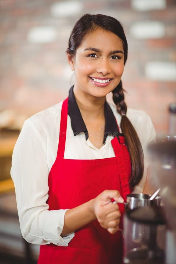 Het glimlachen barista die melk stomen bij de koffiemachine stock foto's