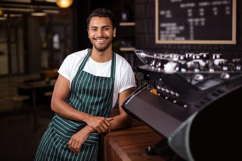 Het glimlachen barista die tegen teller leunen stock fotografie