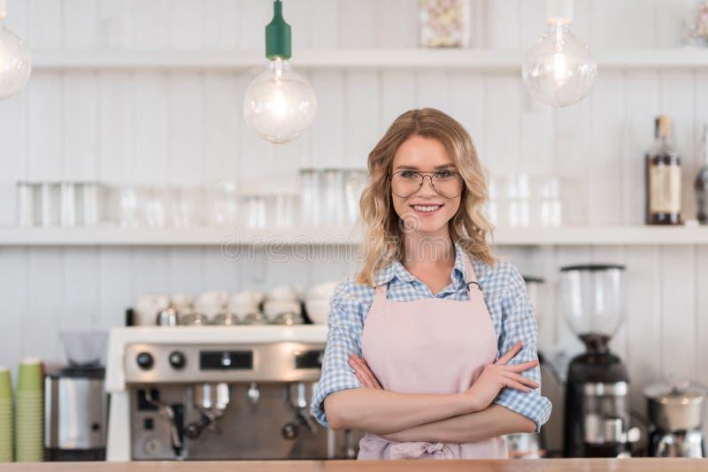 Het glimlachen barista die zich bij teller tijdens het werk in koffie bevinden royalty-vrije stock afbeelding