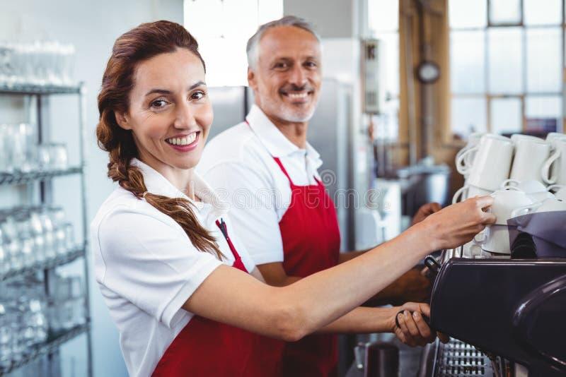 Het glimlachen barista gebruikend de koffiemachine met erachter collega royalty-vrije stock foto's