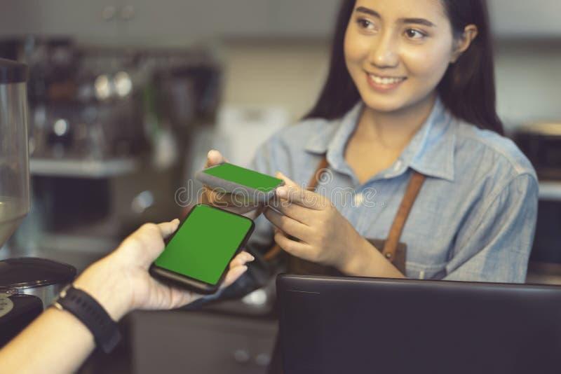 Het glimlachen barista gebruikend smartphone en nfs technologie om klant te helpen voor een aankoop met telefoon bij een koffie b royalty-vrije stock fotografie