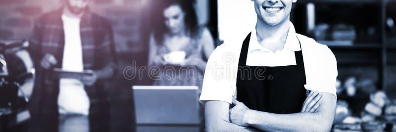 Het glimlachen barista met wapens voor klanten worden gekruist die royalty-vrije stock fotografie