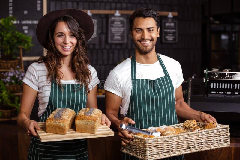 Het glimlachen baristas die brood en desserts houden royalty-vrije stock afbeelding