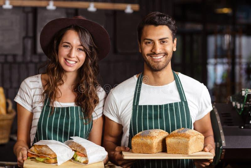 Het glimlachen baristas die brood en sandwiches houden stock afbeelding