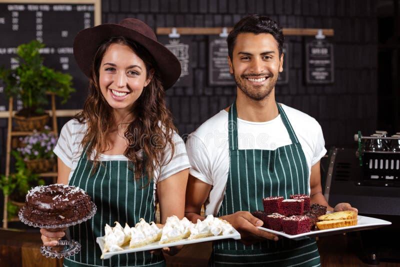 Het glimlachen baristas die dienbladen met desserts houden stock afbeelding