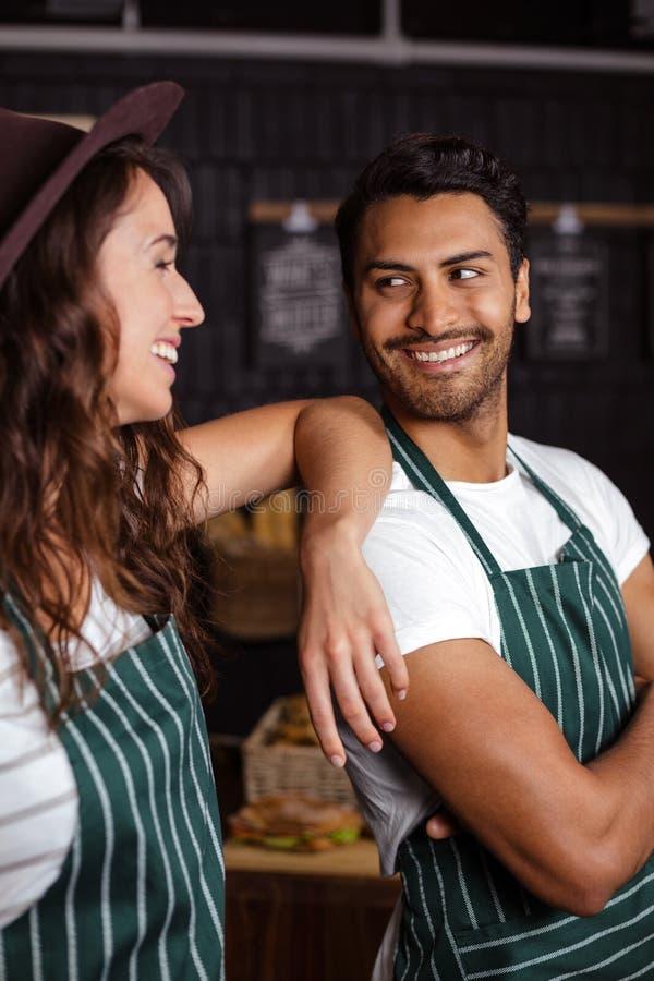 Het glimlachen baristas die elkaar bekijken stock afbeeldingen