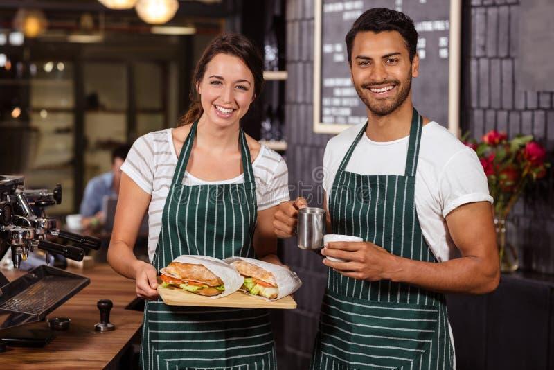 Het glimlachen baristas die sandwiches en hete melk houden royalty-vrije stock afbeeldingen