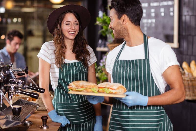 Het glimlachen baristas die sandwiches houden royalty-vrije stock afbeelding