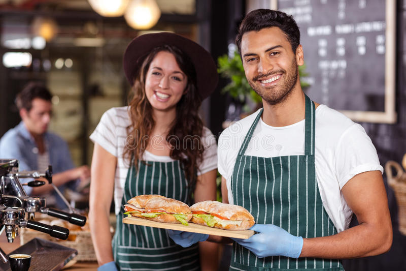 Het glimlachen baristas die sandwiches houden royalty-vrije stock fotografie