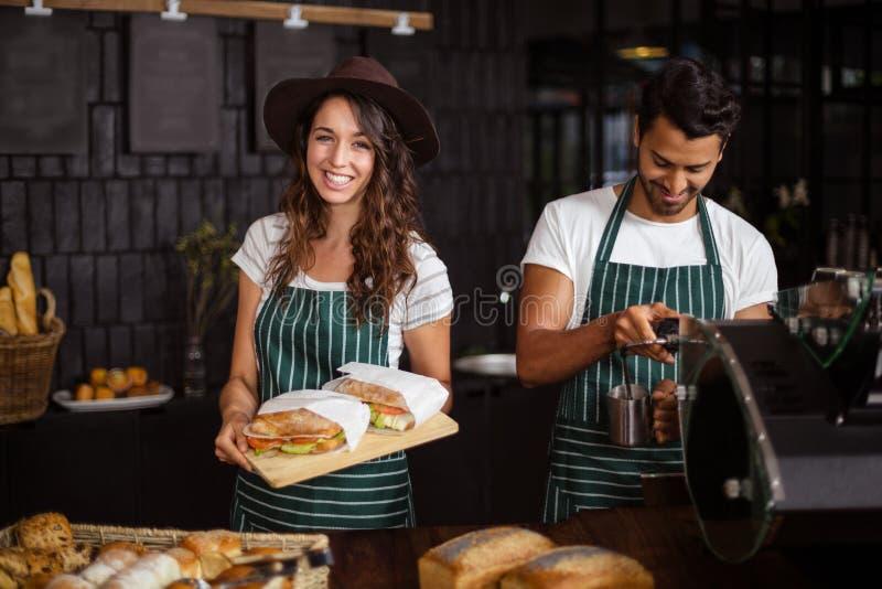 Het glimlachen baristas die sandwiches houden en het maken van koffie royalty-vrije stock afbeelding