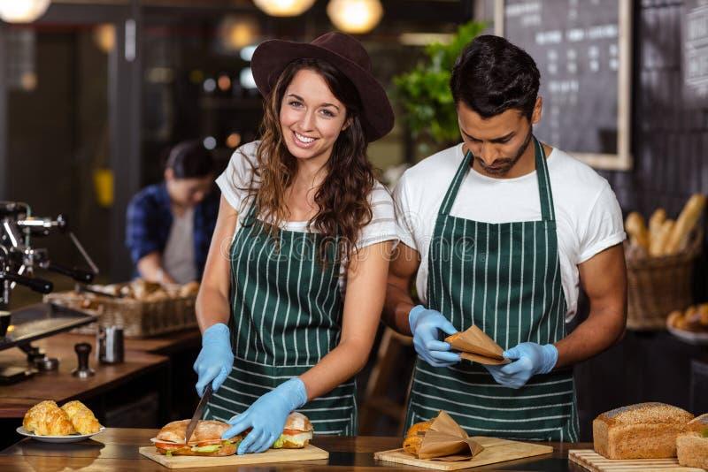Het glimlachen baristas die sandwiches voorbereiden royalty-vrije stock afbeeldingen