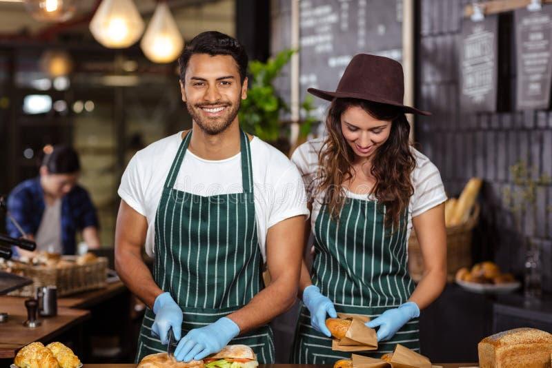 Het glimlachen baristas die sandwiches voorbereiden royalty-vrije stock fotografie