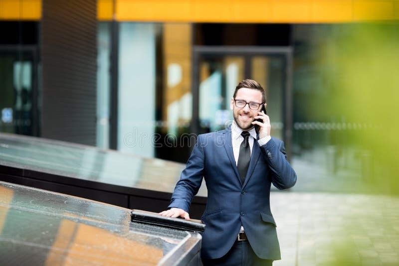Het glimlachen het bedrijfsmens spreken smartphone dichtbij de bureaubouw royalty-vrije stock fotografie