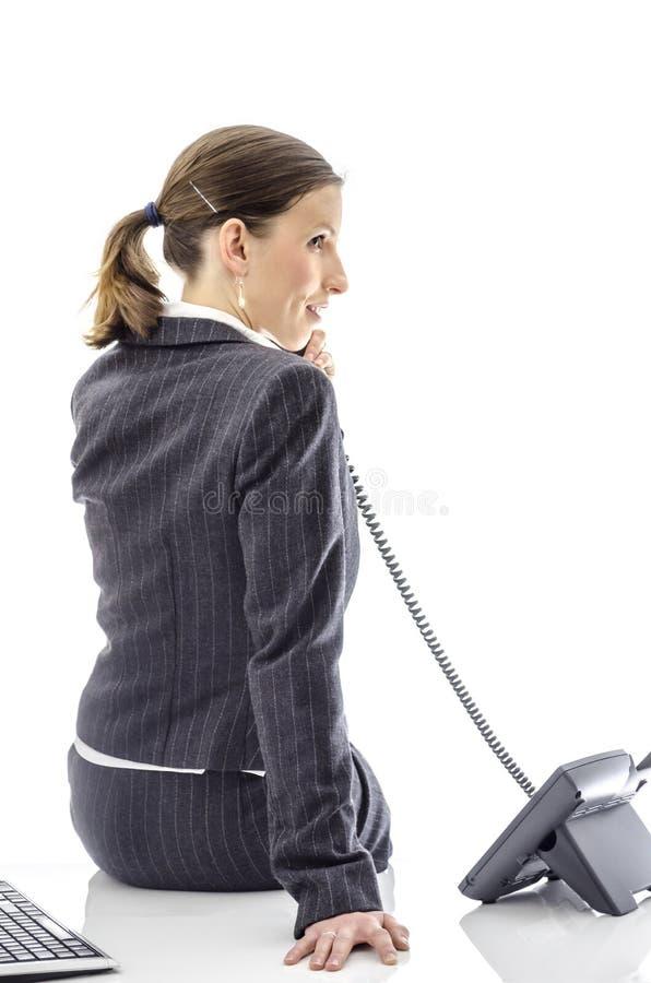 Het glimlachen bedrijfsvrouwenzitting op een wit bureau stock fotografie