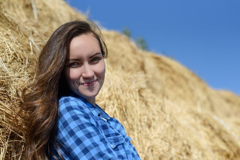 Het glimlachen bevindt het jonge brunette zich leunend op een hooiberg in een blauw overhemd van de mensen` s plaid, exemplaarrui stock fotografie