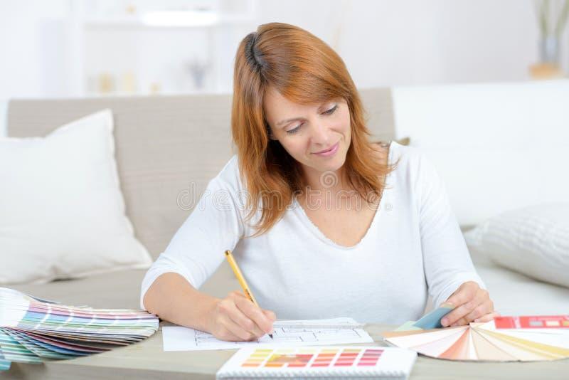 Het glimlachen binnenlandse deigner bij bureau die met kleurengrafieken werken royalty-vrije stock afbeeldingen