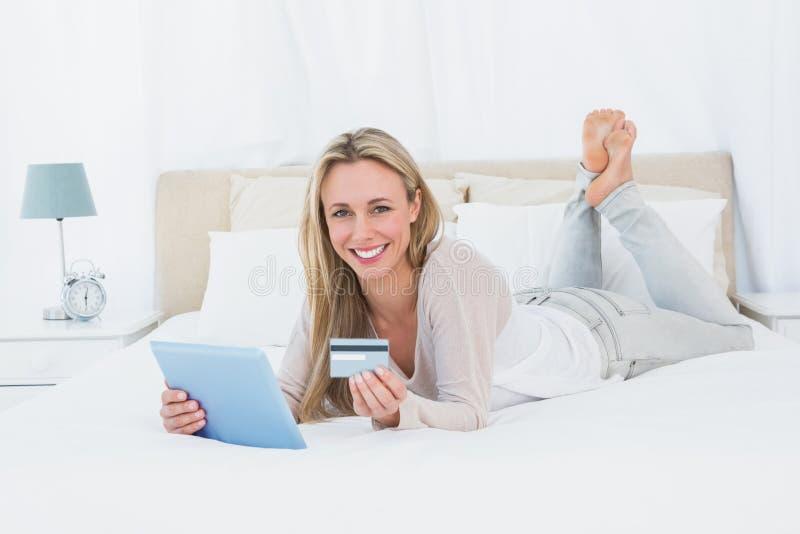 Het glimlachen blonde winkelen online met tablet royalty-vrije stock fotografie