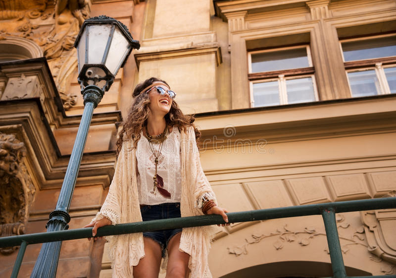 Het glimlachen boho elegant met zonnebril dichtbij oude stadsstraatlantaarn royalty-vrije stock foto's