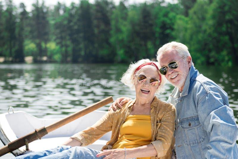 Het glimlachen in boot Positief actief paar van en gepensioneerden die gelukkig terwijl het zitten in hun kleine boot glimlachen  stock afbeelding