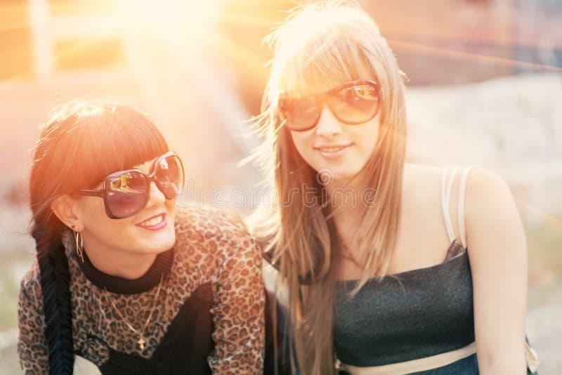 Het glimlachen brunette en blobde vrouwen backlit door zonsondergang stock fotografie
