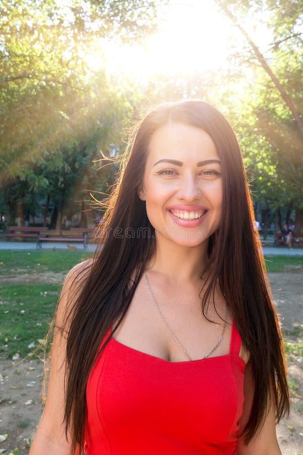 Het glimlachen brunette met de zon bij achtergrond stock foto