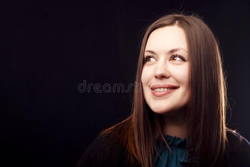 Het glimlachen brunette op zwarte stock foto's