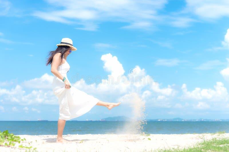 Het glimlachen de Aziatische vrouw witte het dragen manierzomer die op het zandige oceaanstrand lopen De vrouw geniet en ontspant stock foto's