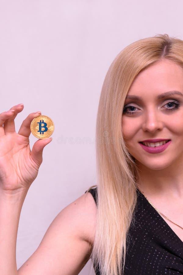 Het glimlachen de greep gouden bitcoin van het blondemeisje in twee vingers stock afbeeldingen