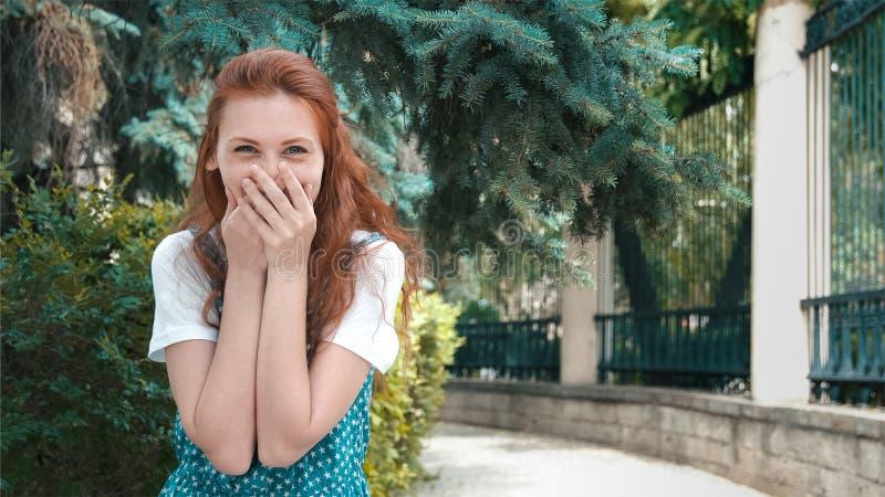 Het glimlachen de mooie lach van het roodharigemeisje bij grap stock afbeeldingen