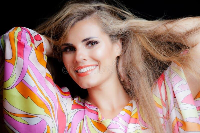 Het glimlachen de schoonheidsportret van het blondemeisje in zijdeachtige kleurrijke kleding royalty-vrije stock afbeeldingen