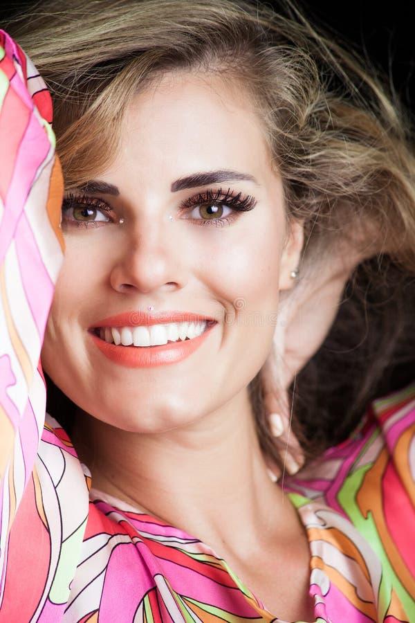 Het glimlachen de schoonheidsportret van het blondemeisje in zijdeachtige kleurrijke kleding royalty-vrije stock fotografie