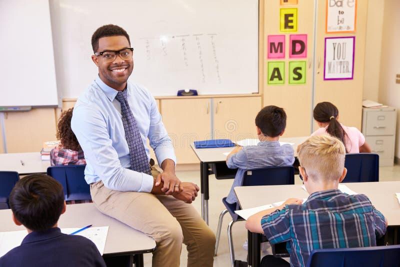 Het glimlachen de zitting van de basisschoolleraar op een pupilï¿ ½ s bureau royalty-vrije stock afbeelding