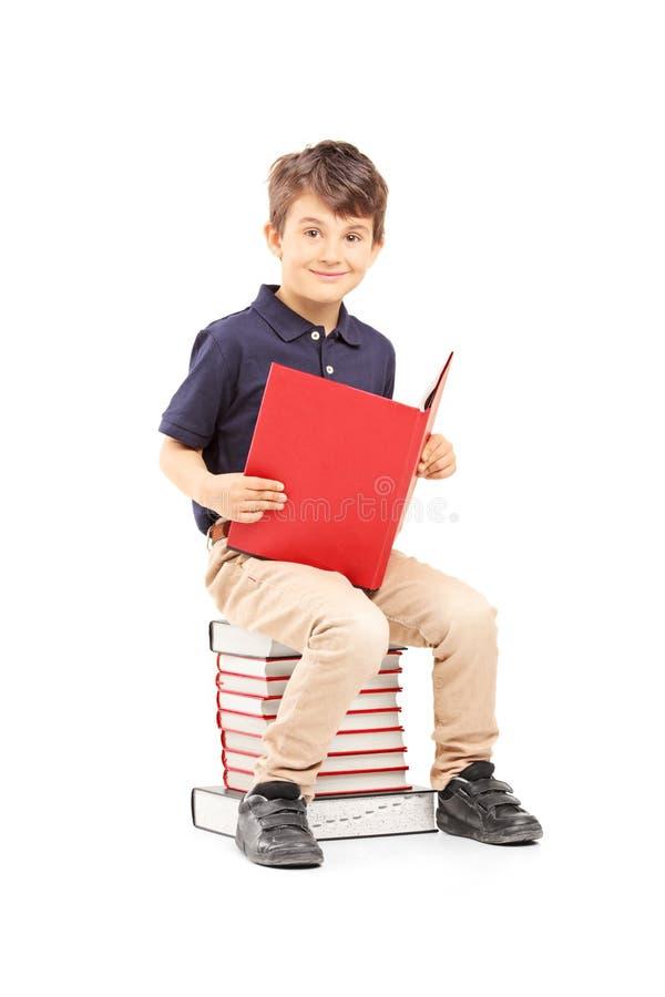 Het glimlachen de zitting van de schooljongen op een stapel van boeken en lezing stock fotografie