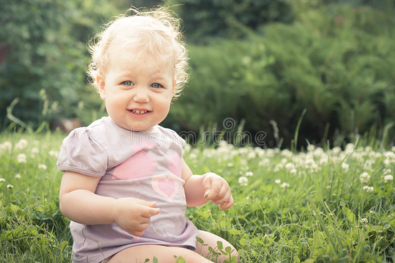 Het glimlachen de zitting van het babymeisje in gras onder het tot bloei komen bloeit in de zomerpark in zonnige dag met exemplaa stock afbeeldingen