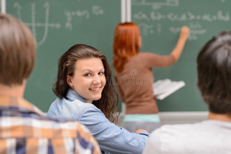 Het glimlachen de zitting van het studentenmeisje in wiskundeklaslokaal royalty-vrije stock afbeeldingen