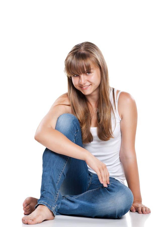 Het glimlachen de zitting van het tienermeisje stock foto