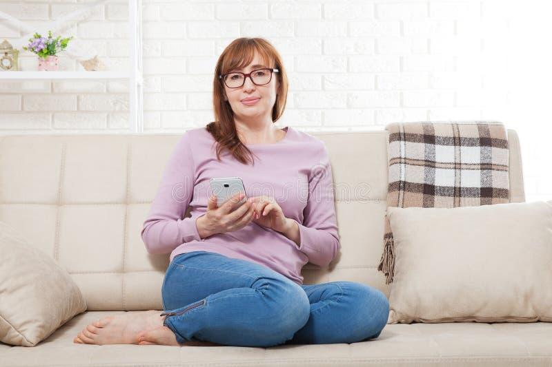 Het glimlachen de zitting van de middenleeftijdsvrouw op bank en het typen bericht op slimme telefoon thuis Huisvrouw die online  stock afbeeldingen