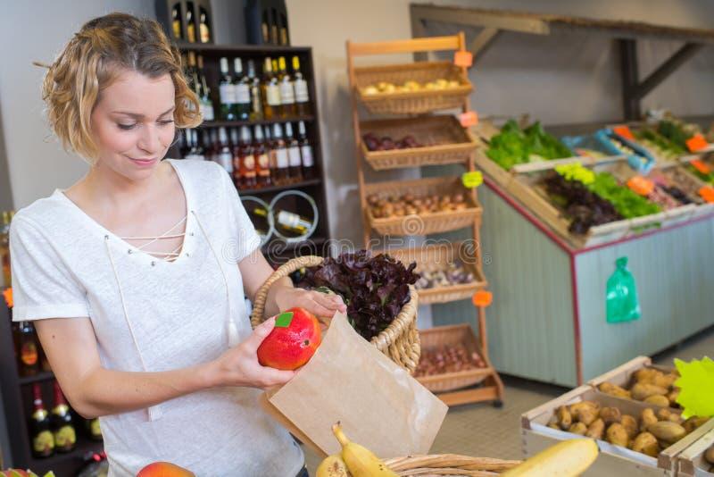 Het glimlachen dient vrouwelijke holdings verse peper binnen voedselopslag in royalty-vrije stock foto's