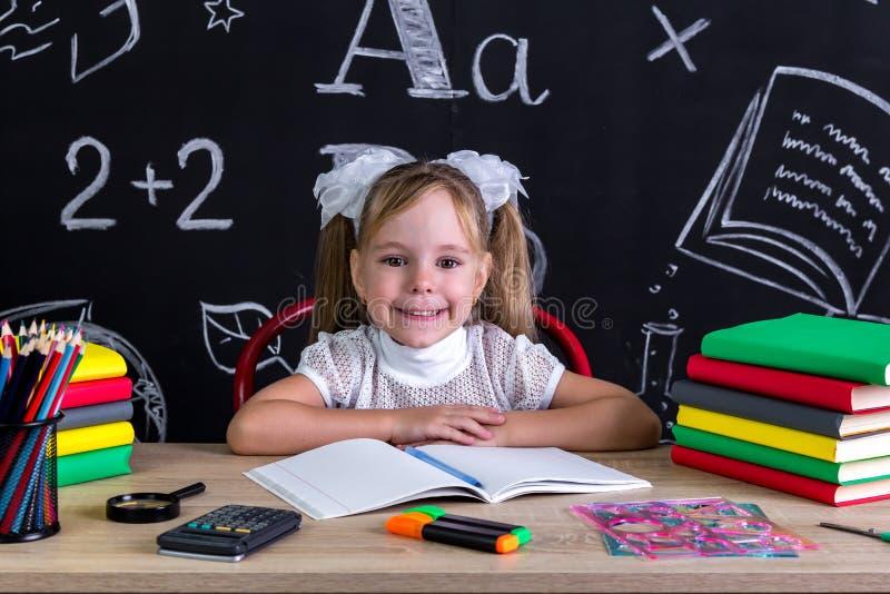 Het glimlachen en gelukkige meisjeszitting bij het bureau met boeken, schoollevering stock foto's
