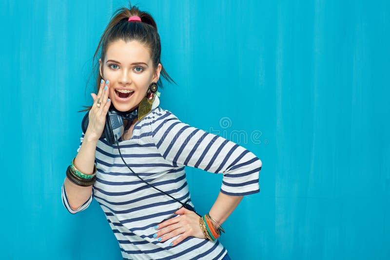 Het glimlachen het gelukkige portret van het tienermeisje op blauwe muurachtergrond stock afbeelding