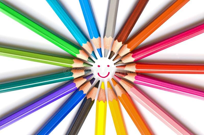Het glimlachen gezicht in een geïsoleerde cirkel van kleurrijke houten potloden op wit, schoolkunst en onderwijsconcept dat wordt stock foto